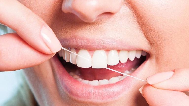 Woman Flossing Teeth | Groves Dental Care